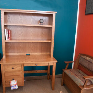 wood desk with shelves above and bench besides