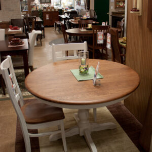 solid cherry 48 inch round dining table with painted ladder backed chairs at fireside with more of our selection behind